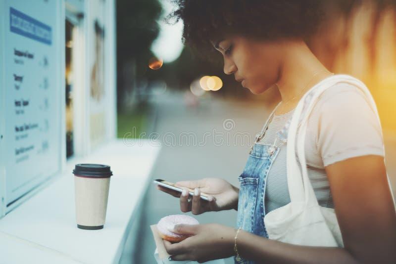 Zwart meisje het posten beeld van doughnut aan sociale netwerken stock foto's