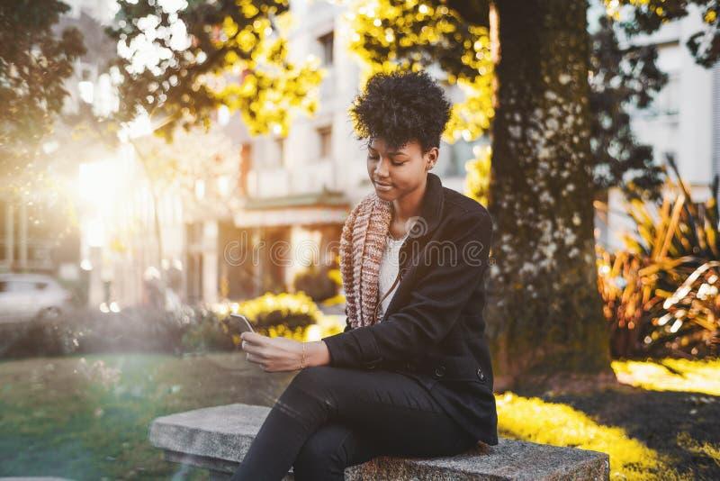 Zwart meisje op bank in park met smartphone stock afbeelding