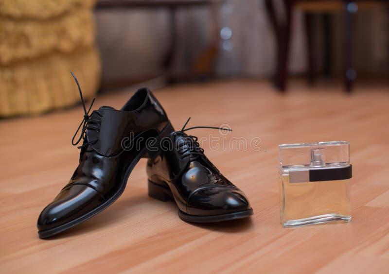 Zwart mensen` s schoenen en parfum voor huwelijksvoorbereiding royalty-vrije stock afbeeldingen