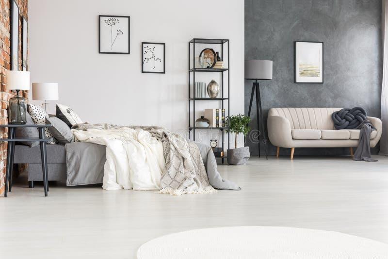 Zwart meubilair, modieuze bank en een comfortabel tweepersoonsbed in een spaciou stock foto's