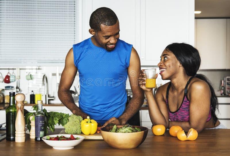 Zwart paar die gezond voedsel in de keuken koken stock foto