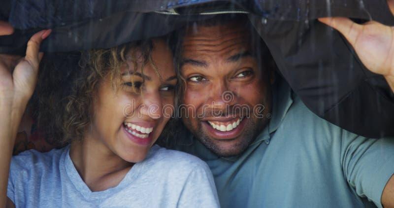Zwart paar die zich onder laag bevinden die niet nat proberen te worden stock fotografie