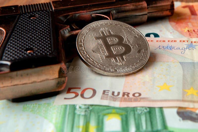 Zwart pistool, euro en muntstuk in de vorm van bitcoin op houten achtergrond royalty-vrije stock foto's