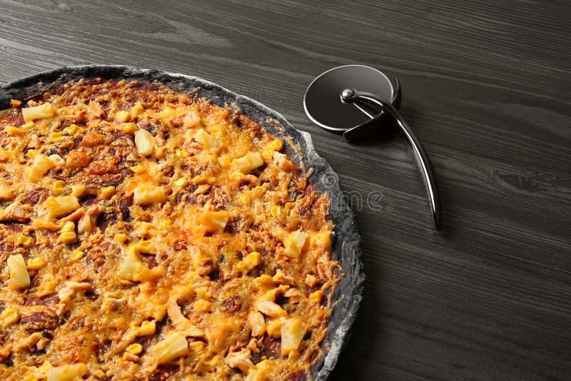 Zwart pizza en mes op houten lijst, close-up stock afbeeldingen