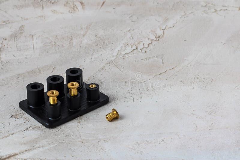 Zwart plastic detail met omhoog gemaakt van gouden kleurenmetaal op de grijze cementachtergrond royalty-vrije stock fotografie