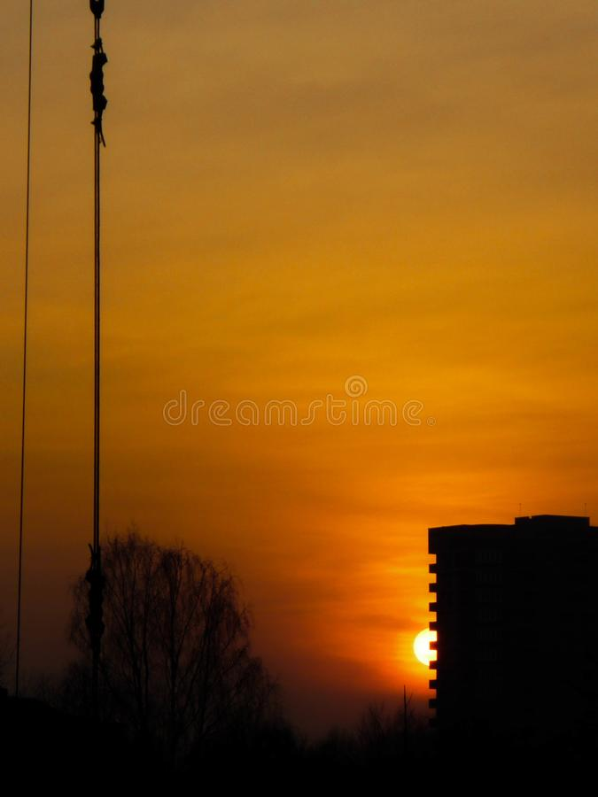 Zwart silhouet van een gebouw met meerdere verdiepingen tegen de oranje zonsondergang De bouw van een huis tegen de zon stock afbeelding