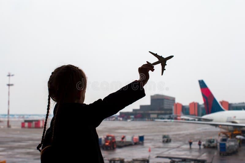 Zwart silhouet van een klein vliegtuig modelstuk speelgoed op luchthaven in jonge geitjeshanden stock afbeeldingen