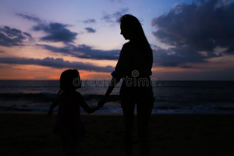 Zwart silhouet van jonge vrouwelijke persoon die met meisje dichtbij overzees op zonsondergangachtergrond lopen stock afbeelding