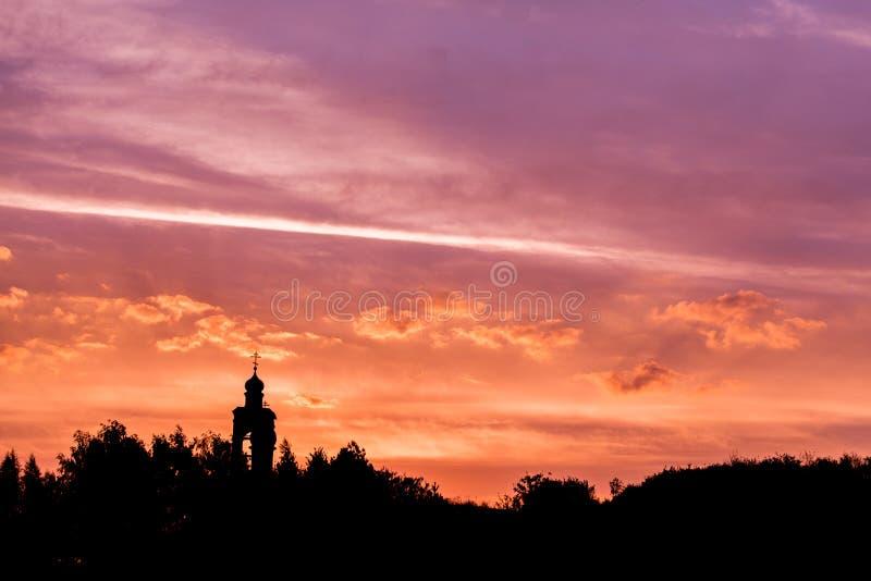 Zwart silhouet van kerk en boshorizon op gouden-purpere zonsonderganghemel met zachte wolken royalty-vrije stock foto's