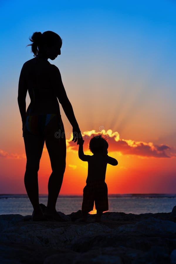 Zwart silhouet van moeder, de gang van de babyzoon door overzees strand stock afbeeldingen