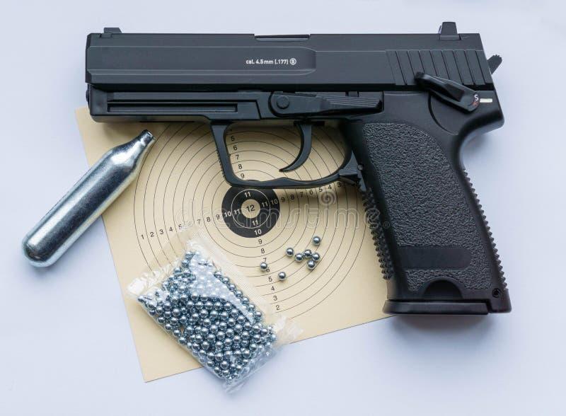 Zwart sportenpistool met doel, kogels en samengeperste lucht stock fotografie