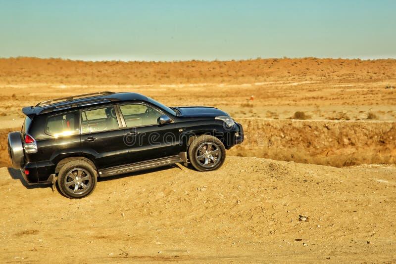 Zwart SUV en het Reuzegas krateen vormen in in Turkmenistan ` Poorten van Hel ` stock afbeelding