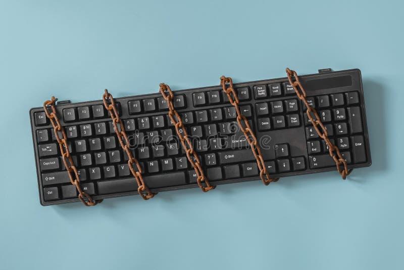 Zwart toetsenbord met een gerolde ketting Concept op het gebied van censuur of persvrijheid royalty-vrije stock afbeeldingen