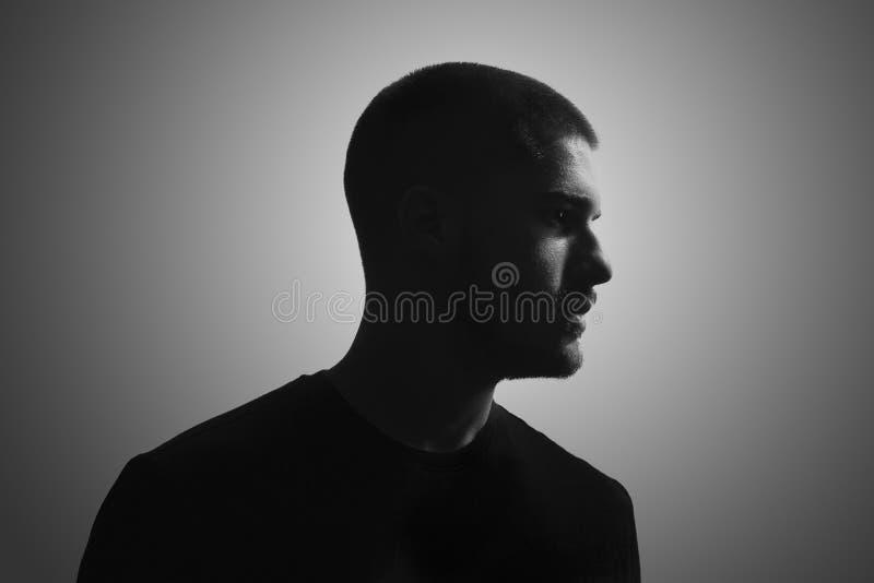 Zwart-wit, één jonge mens, 20-25 jaar, humeurig donker portret, stock afbeelding