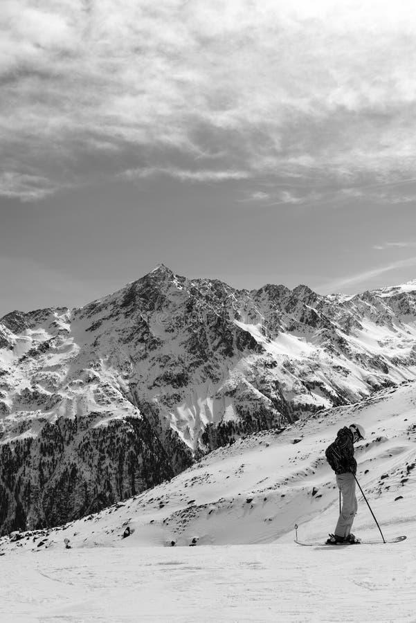 Zwart-wit Alpien landschap en de skiër in de voorgrond royalty-vrije stock fotografie
