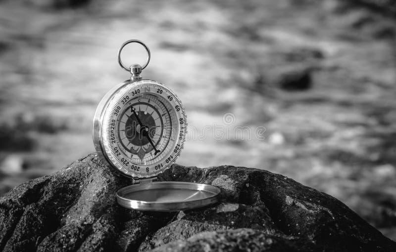 Zwart-wit analoog die kompas op de rotsen wordt verlaten royalty-vrije stock afbeeldingen