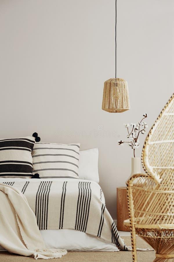Zwart-wit beddegoed op het bed van de koningsgrootte in elegant slaapkamerbinnenland met van het pauwstoel en exemplaar ruimte op royalty-vrije stock afbeeldingen