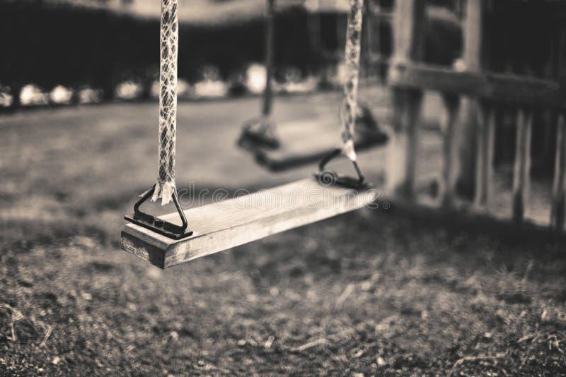 Zwart-wit beeld lege schommeling bij de speelplaats in de zomer, horizo royalty-vrije stock afbeeldingen