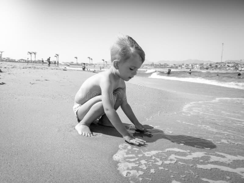 Zwart-wit beeld van aanbiddelijke 3 jaar het oude peuterjongen spelen met natte zand en overzeese golven op het strand bij helder stock foto