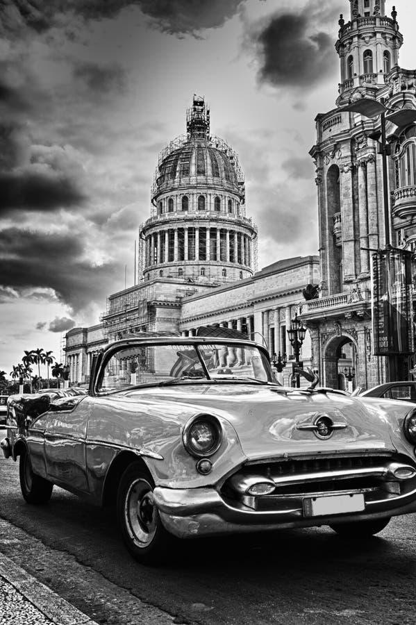Zwart-wit beeld van de straat van Havana met uitstekende auto en Capi stock fotografie