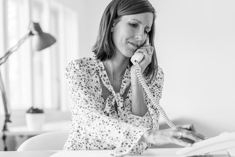 Zwart-wit beeld van een bedrijfsvrouw die een telefoongesprek maken royalty-vrije stock fotografie