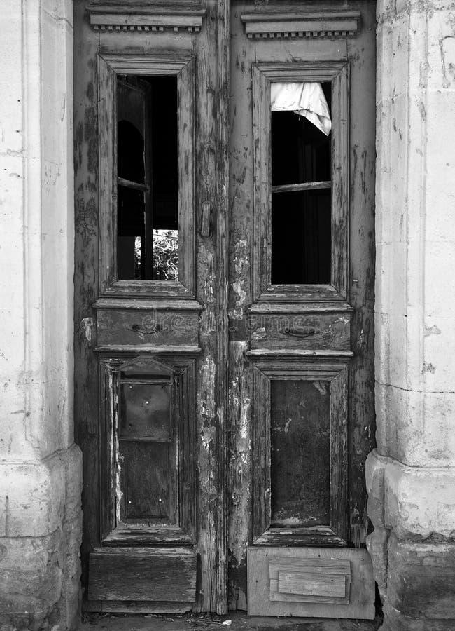 Zwart-wit beeld van een gebroken oude dubbele deur in een verlaten verlaten huis met gebroken vensters en langzaam verdwenen pell royalty-vrije stock fotografie