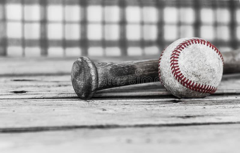 Zwart-wit beeld van een honkbal en een knuppel op houten oppervlakte stock afbeelding