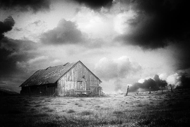 Zwart-wit beeld van een oude verlaten schuur op een stormachtige nacht stock afbeelding