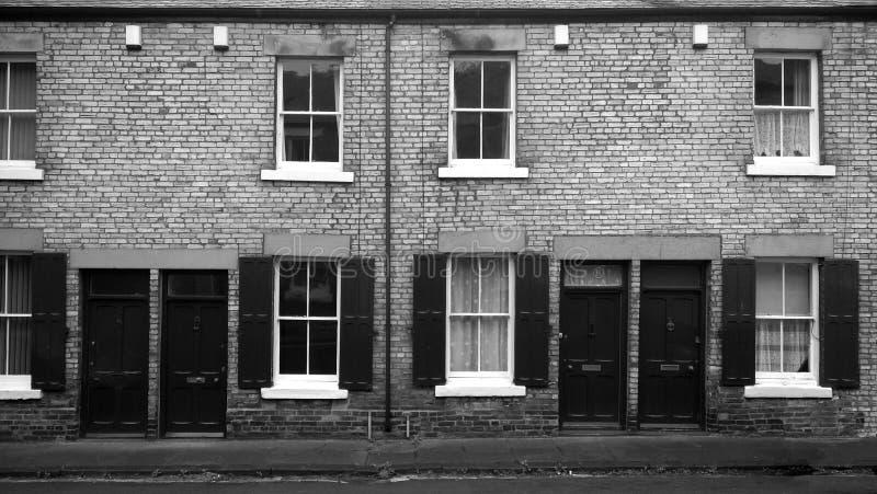 Zwart-wit beeld van een rij van typische noordelijke Engelse arbeidende klasse terrasvormige huizen met deuren die rechtdoor voor stock afbeelding