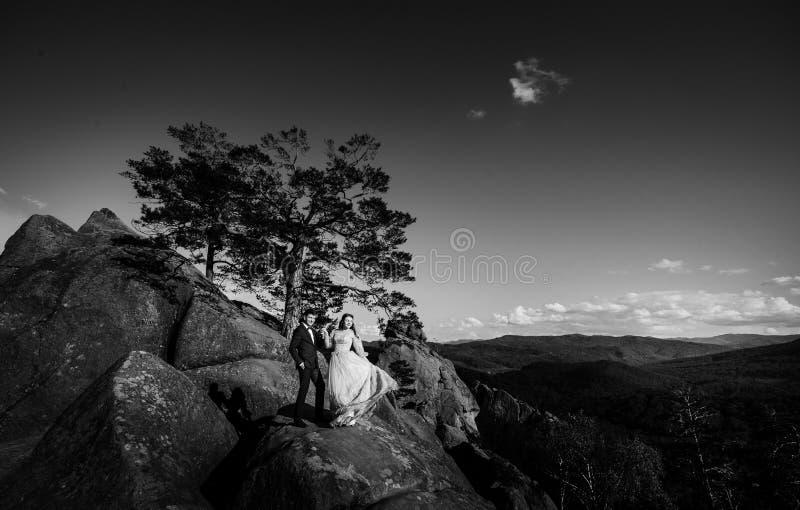 Zwart-wit beeld van het schitterende paar stellen op de rotsen royalty-vrije stock foto