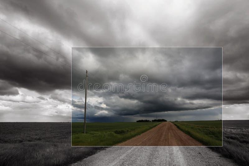 Zwart-wit beeld van prairieonweer met grintweg die tot horizon leiden stock fotografie