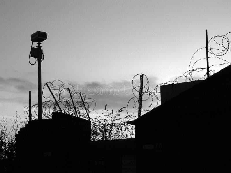 Zwart-wit beeld van prikkeldraad op een muur in silhouet en veiligheidscamera tegen een bewolkte avondhemel stock foto's