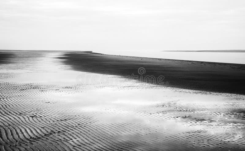 Zwart-wit beeld van strandlandschap bij hoogtijd royalty-vrije stock afbeeldingen