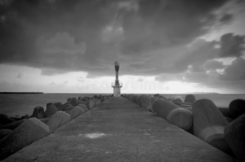Zwart-wit beeld van vuurtoren met donkere en dramatische wolken tijdens moessonseizoen stock fotografie