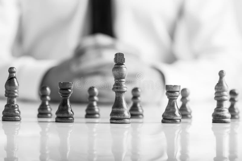 Zwart-wit beeld van zakenmanzitting voor donker schaak p stock afbeelding