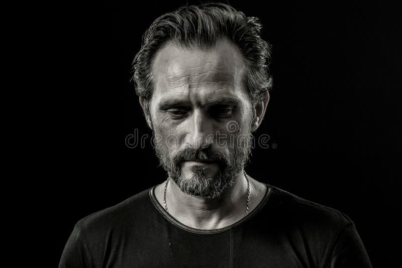 Zwart-wit dicht omhooggaand portret van een strenge mens met droevige gelaatsuitdrukking stock afbeelding
