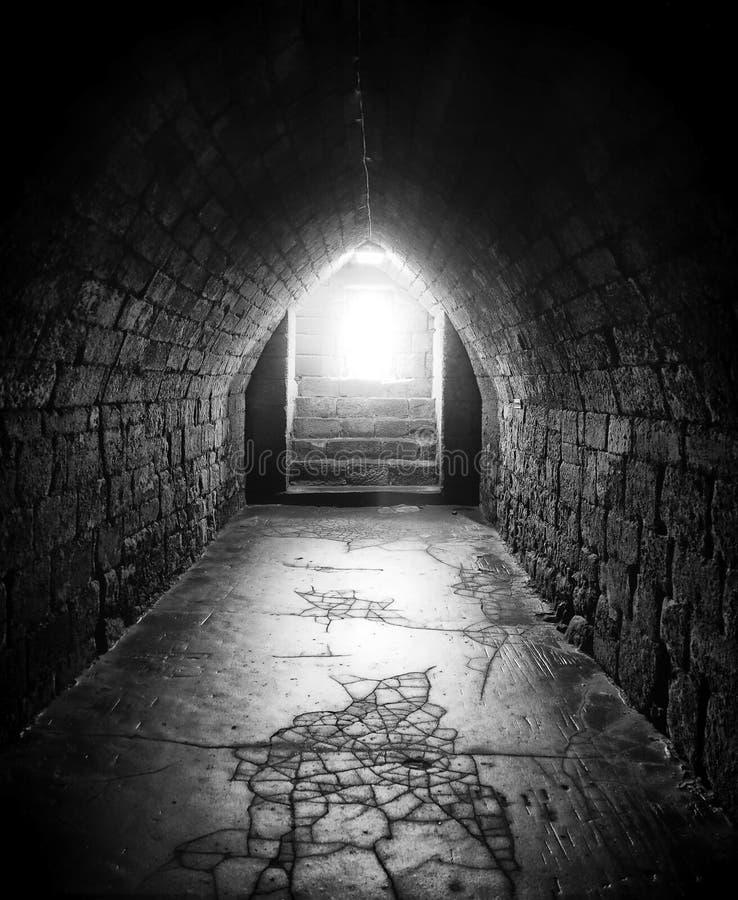 Zwart-wit donker beeld van een oude ondergrondse voetvoettunnel met muren van een de overspannen dakensteen en een gebarsten vloe stock foto's