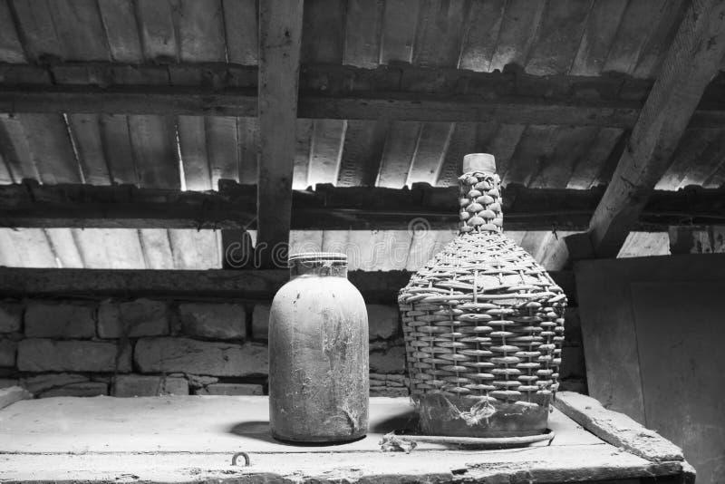 Zwart-wit glas, houten en metaalvoorwerpen in de zolder met stof en spiderwebs royalty-vrije stock afbeelding