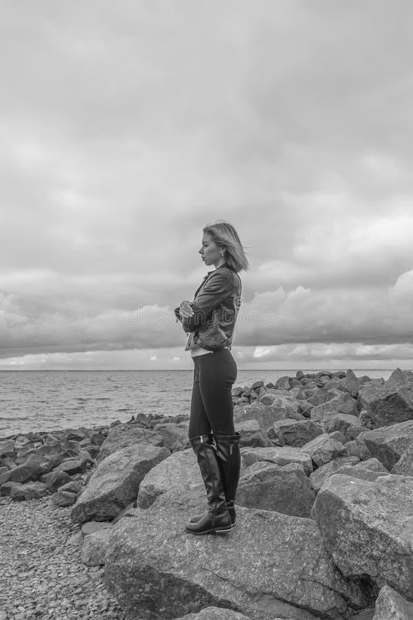 Zwart-wit, op een klip tegen de hemel, een mooi meisje stock afbeeldingen