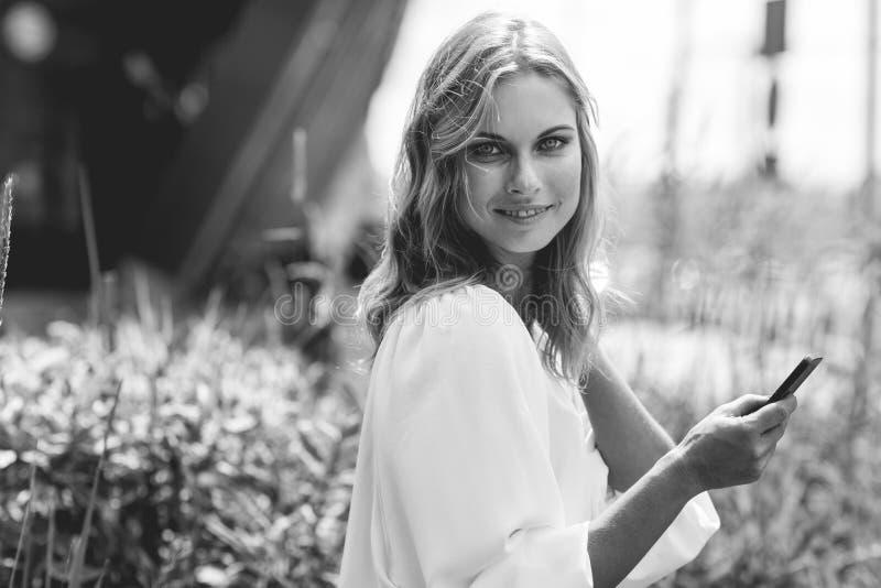Zwart-wit in openlucht portret van zachte vrouw met cellphone stock foto's