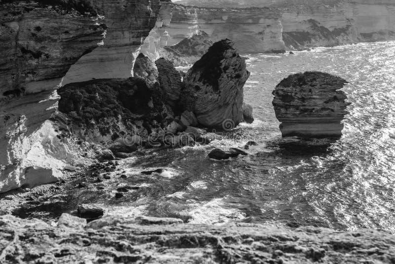 Zwart-wit panorama van thr rotsachtige overzeese kust met duidelijk transparant blauw water, klippen, reusachtige rotsen, gras Bo stock afbeelding