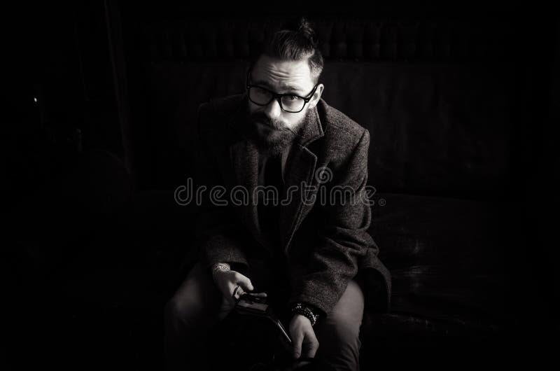 Zwart-wit Portret van de knappe volwassen mens die een tekstbericht, de berichten van de bedrijfsmensenlezing, het modieuze donke stock afbeelding