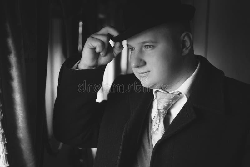 Zwart-wit portret van de mens in bowlingspelerhoed die uit trein kijken royalty-vrije stock foto's