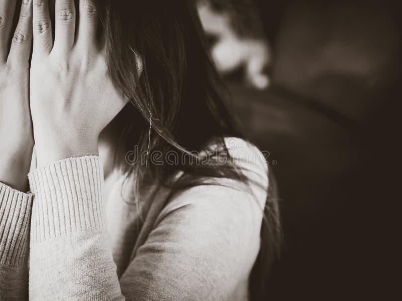 Zwart-wit portret van droevige jonge vrouwenzitting door bank stock foto