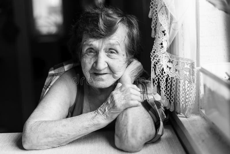 Zwart-wit portret van een bejaarde gelukkige vrouw royalty-vrije stock afbeelding