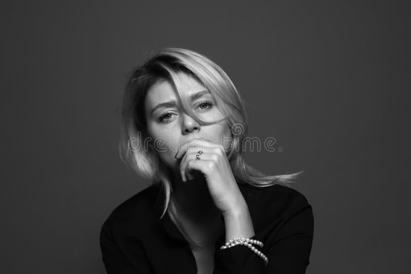 Zwart-wit portret van een droevige jonge vrouw, die aan de camera kijken, die handen op haar mond houden stock fotografie