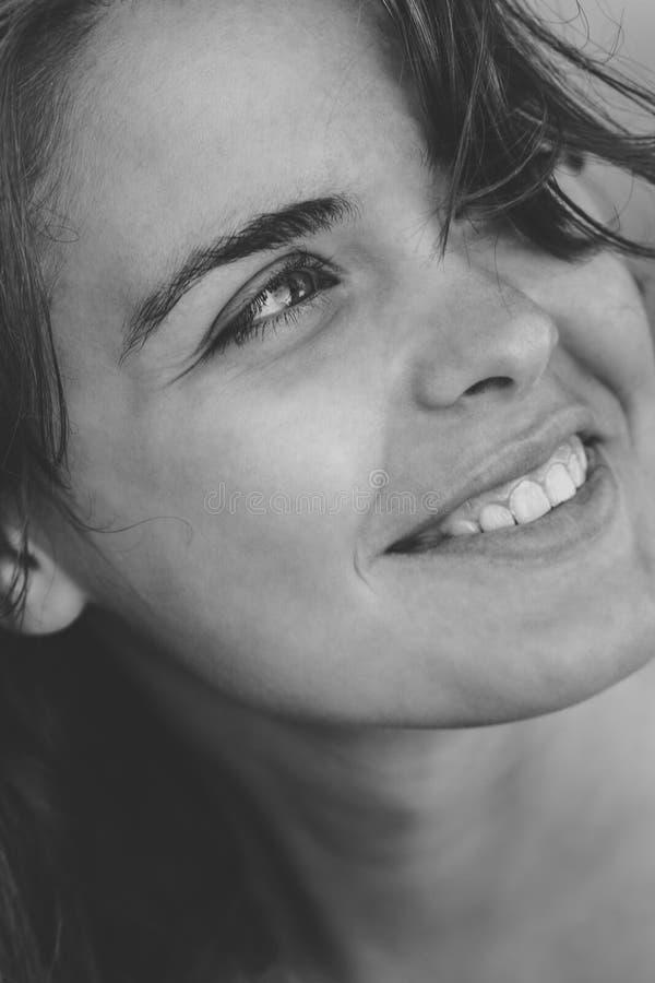 Zwart-wit portret van een gelukkige jonge mooie vrouw die geen geheim van hun positieve emoties maakt en de binnenwereld opent stock afbeelding