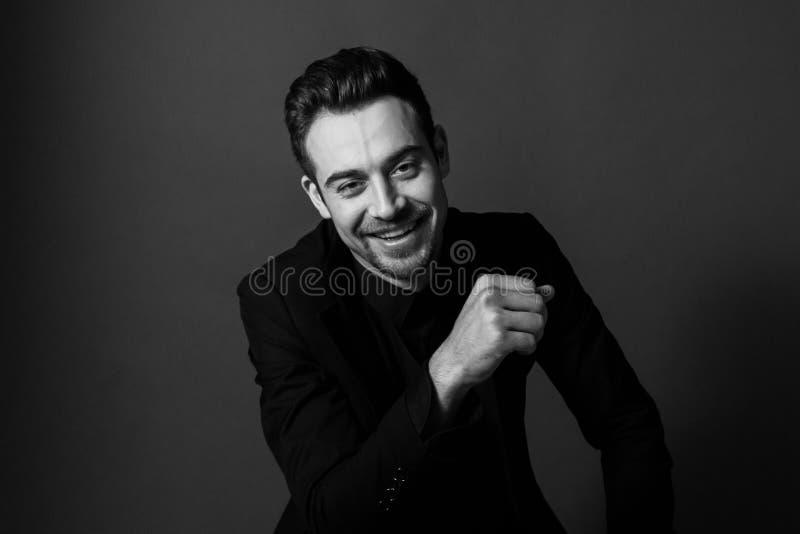 Zwart-wit portret van een glimlachende jonge knappe mens in een kostuum stock fotografie