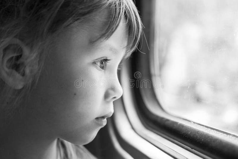Zwart-wit portret van een mooi meisje dat in het venster van de trein kijkt Close-up van een droevig kind die door venster kijken royalty-vrije stock afbeeldingen