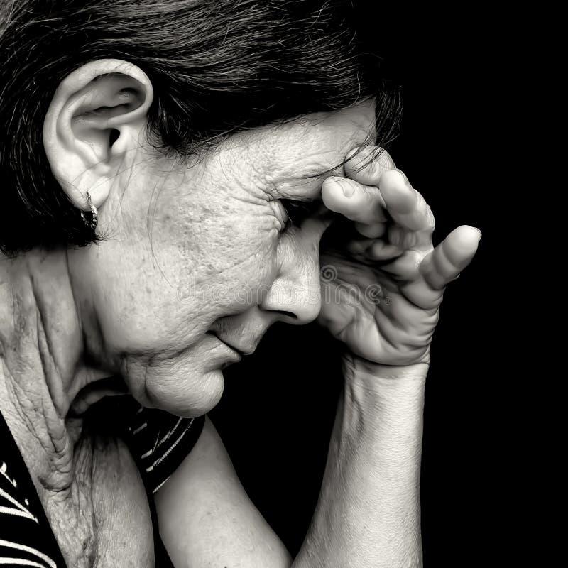 Zwart-wit portret van een zeer droevige oude vrouw stock afbeelding